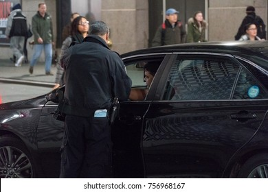 New York City, Circa 2017: NYPD police officer pulls over livery cab driver and checks license and registration identification. Night time during rush hour on manhattan street