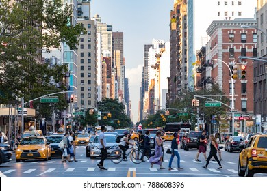 NEW YORK CITY - CIRCA 2017: Busy crowds of people walk across 3rd Avenue in front of rush hour traffic in the East Village neighborhood of Manhattan in New York City.