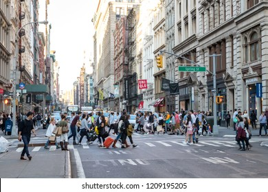 NEW YORK CITY, CIRCA 2018: Busy crowds of people walk across the intersection of Broadway and Spring Street in the SoHo neighborhood of Manhattan, NYC.