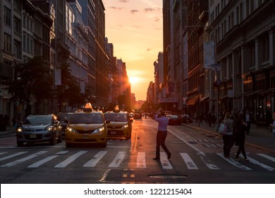 NEW YORK CITY, CIRCA 2018: Man stands in the middle of the intersection on 23rd Street in taking a photo of the evening sunset in Manhattan, New York City