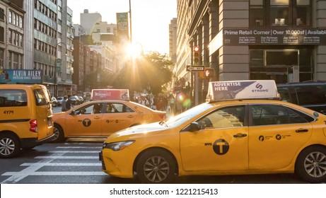 NEW YORK CITY, CIRCA 2018: Yellow taxi cabs drive through a busy intersection on 5th Avenue with sunlight shining in the background of the Manhattan skyline.