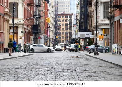 NEW YORK CITY - CIRCA 2019: Cobblestone covered Greene Street in SoHo is busy with cars and people in Manhattan NYC.