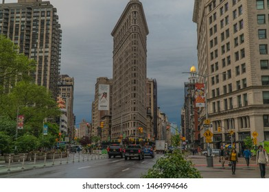 New York City, Circa 2019: Flat Iron building wide exterior establishing shot street view during morning rush hour commute. People walk along side walk and uber ride share transportation drives by