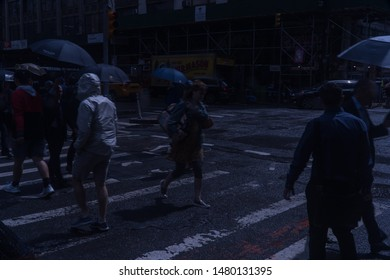 New York City, Circa 2019: Night time view of Manhattan crosswalk during evening commute in the rain. Poncho and umbrella coverings keep pedestrians dry