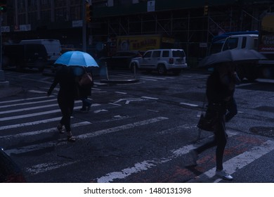 New York City, Circa 2019: Night time view of Manhattan crosswalk during rush hour in the rain. Blue umbrella stands out of darkness under colorful moon light scene