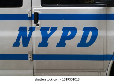 New York City, Circa 2019: NYPD Police Department logo letters painted on cop vehicle patrol car door parked on Manhattan roadway during day time