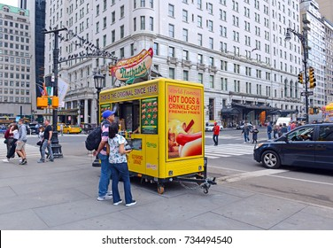 NEW YORK CITY CIRCA OCTOBER 2017. Food cart operators such as this hot dog vendor compete heavily for top spots near popular tourist hubs which can many times as lucrative as quieter locations.