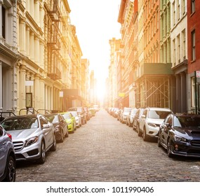 New York City cobblestone street scene with buildings and cars in the historic SoHo neighborhood of Manhattan with sunlight background