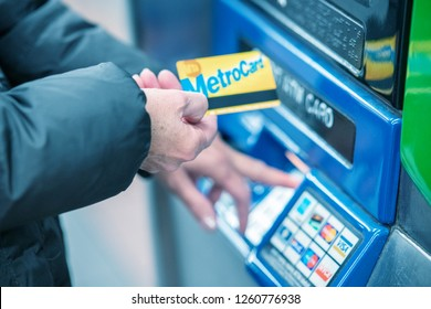 NEW YORK CITY - DECEMBER 1, 2018: Woman charges her metrocard at a fill station. Metrocard allows you to travel on  NYC public transport.