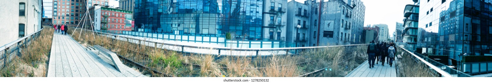 NEW YORK CITY - DECEMBER 1ST, 2018: Panoramic view of tourists along High Line Park. The city attracts 50 million tourists annually.