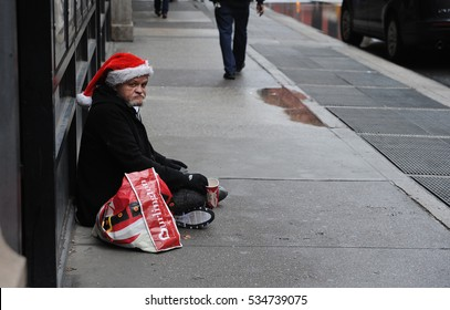 NEW YORK CITY - DECEMBER 2016: A homeless man wearing a Santa hat asks for help while sitting on Broadway in Manhattan.