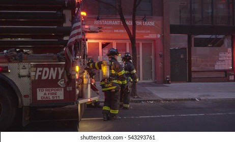 New York City - December 2016: FDNY Fire Department firefighters stand next to an emergency response truck at emergency scene in lower Manhattan