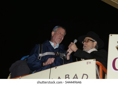 NEW YORK CITY - DECEMBER 24 2016: Chabad of Park Slope sponsored its annual giant menorah lighting in Grand Army Plaza to mark the first night of Hanukkah. Mayor de Blasio with Shimon Hecht aloft