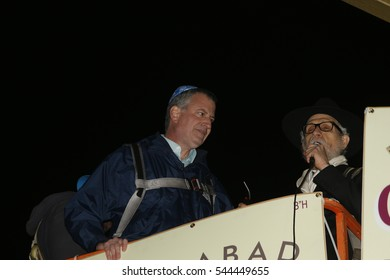 NEW YORK CITY - DECEMBER 24 2016: Chabad of Park Slope sponsored its annual giant menorah lighting in Grand Army Plaza to mark the first night of Hanukkah. Mayor de Blasio with Rabbi Hecht aloft