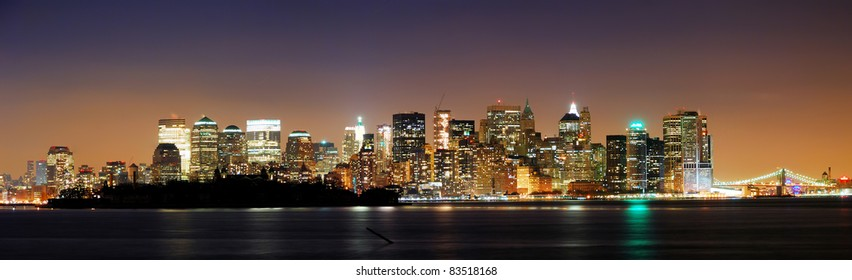 New York City downtown night skyline panorama over Hudson river with skyscrapers.