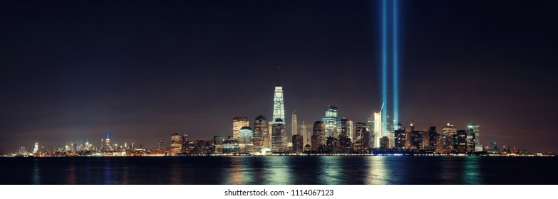 New York City downtown skyline at night panorama over Hudson River and September 11 tribute light