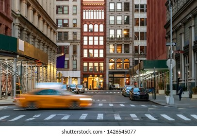 New York City evening street view of the intersection of Washington Place and Broadway in the Greenwich village neighborhood of Manhattan with speeding taxi cab