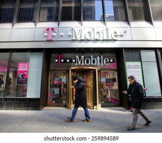 NEW YORK CITY - FEB. 25, 2015:  Pedestrians walk past a T-Mobile retail store. T-Mobile International AG is a holding company for Deutsche Telekom AG's  communications subsidiaries outside Germany.