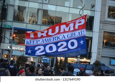 """New York City, February 19, 2019 - Counter protester at an rally against President Trump's National Emergency waving a large """"Make America great Again"""" flag in Union Square, Manhattan."""