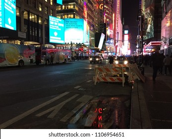 NEW YORK CITY - JANUARY 15, 2018: View of Times Square at night with reflection of sign in puddle with neon lights and car headlights billboards advertisments