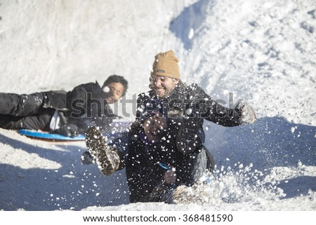 NEW YORK CITY - JANUARY 24 2015: Brooklyn residents slide, build snow structures & cavort in the snow that filled Prospect Park after NYC's record-breaking blizzard.