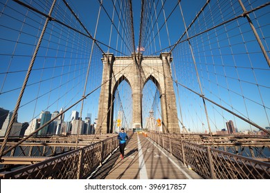 NEW YORK CITY - JANUARY 3: An unidentified woman jogs on the pedestrian walkway of the Brooklyn Bridge from Manhattan to Brooklyn on January 3, 2016 in New York City.