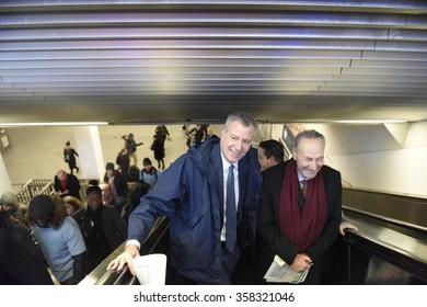 NEW YORK CITY - JANUARY 4 2015: Mayor de Blasio & senator Schumer greeted early morning commuters with information about benefits to lower the cost of mass transit. Mayor & senator ride escalator