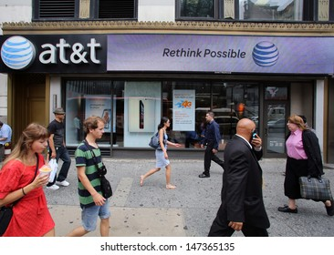 NEW YORK CITY - JULY 11: Pedestrians walk past an AT&T mobile telephone retail outlet  in midtown Manhattan on Thursday, July 11, 2013.