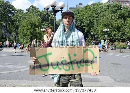 "NEW YORK CITY - JULY 14, 2013: A protestor holds a ""no justice"" sign while others also gather to peacefully protest the Trayvon Martin case in Union Square in Manhattan on July 14, 2013."