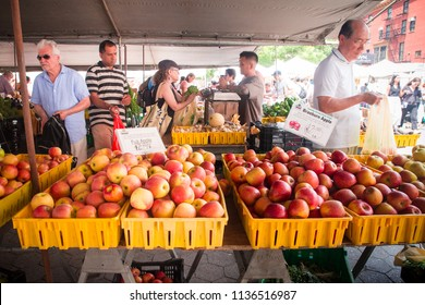 NEW YORK CITY - JULY 16, 2018:  Shoppers buying fruit on display at the Union Square Greenmarket farmers market in Manhattan.