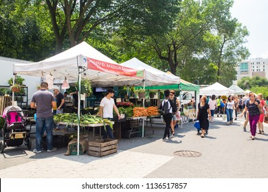 NEW YORK CITY - JULY 16, 2018:  View tents, people and organically grown local fruit and vegetables on display at the Union Square Greenmarket farmers market in Manhattan.