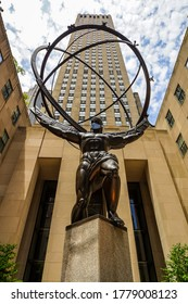 NEW YORK CITY - JULY 16, 2020: Atlas statue by Lee Lawrie with face mask in front of Rockefeller Center in midtown Manhattan during Coronavirus pandemic in New York