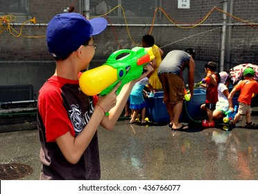 New York City - July 18, 2010:   Children splashing one another with water guns is part of the big fun at the Thingyan Burmese Water Festival