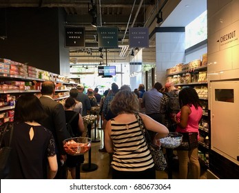 NEW YORK CITY - JULY 18, 2017: Whole Foods Market (WFM). Customers buy at registers from employees. The American supermarket chain acquired by Amazon (AMZN), expanding presence as physical retailer.