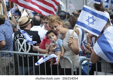 NEW YORK CITY - JULY 20 2014: several thousand supporters of Israeli actions in Gaza staged a rally in Times Square. Parents & child at barrier with US & Israeli flags