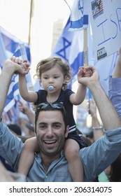 NEW YORK CITY - JULY 20 2014: several thousand supporters of Israeli actions in Gaza staged a rally in Times Square. Baby on father's shoulders with Israeli flags in the background