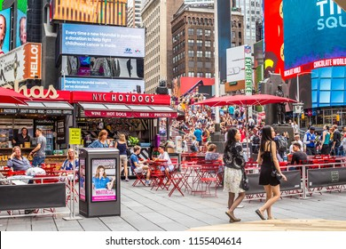 NEW YORK CITY - JULY 26, 2018: View of world famous Times Square in Manhattan with billboards, signs, table and people at the pedestrian plaza on a busy summer day.