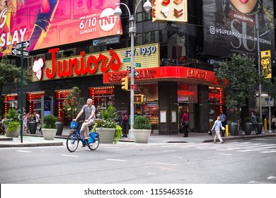 NEW YORK CITY - JULY 26, 2018:  View of Times Square in Manhattan with the famous Junior's Restaurant on the corner and people in view.
