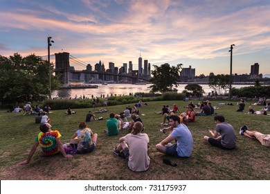 NEW YORK CITY - JULY 3, 2017: People enjoy the sunset over the Manhattan financial district and the East river from the Brooklyn bridge park in New York City.