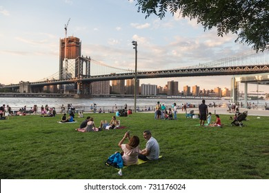 NEW YORK CITY - JULY 3, 2017: People enjoy the sunset over the Manhattan skyline and bridge and the East river from the Brooklyn bridge park in New York City.