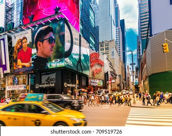 New York City - June 14, 2017: Broadway with street traffic and crowded by many people. The scenery at Times Square in NYC is an iconic landmark famous for tourists as world's busiest pedestrian place