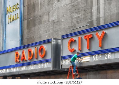 NEW YORK CITY - JUNE 17, 2015: worker changing advertising of Radio City Music Hall, an entertainment venue located in Rockefeller Center