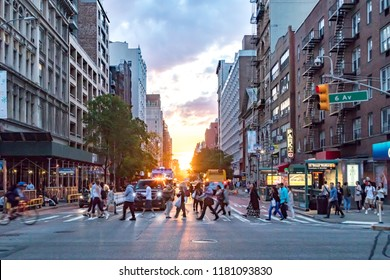 NEW YORK CITY - JUNE, 2018: Crowds of people cross a busy intersection on 23rd Street and 6th Avenue in Manhattan with the colorful sunset in the background skyline