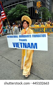 New York City - June 22, 2013:   Vietnamese woman holding sign marching in the International Immigrants Foundation Parade on Avenue of the Americas