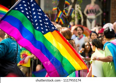 NEW YORK CITY - JUNE 25, 2017: American flag with stars and gay pride rainbow stripes being waved at the annual Gay Pride Parade in Greenwich Village, NYC