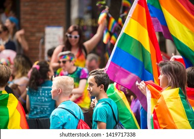 NEW YORK CITY - JUNE 25, 2017: Young participants celebrate at the annual Gay Pride Parade waving rainbow flags as they pass through Greenwich Village.