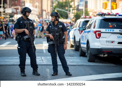 NEW YORK CITY - JUNE 25, 2017: NYPD police officers stand with hands on their weapons, providing security on the sidelines of the annual Gay Pride parade as it passes through Greenwich Village.