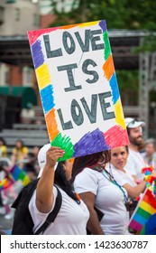 "NEW YORK CITY - JUNE 25, 2017: Supporters hold a sign saying ""Love is Love"" in the annual gay Pride Parade as it passes through Greenwich Village."