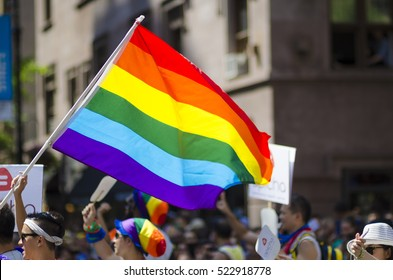 NEW YORK CITY - JUNE 28, 2015: Supporters wave rainbows flags on the sidelines of the annual Pride Parade as it passes through Greenwich Village.