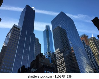 New York City looking up upward view at skyscrapers in day and sunlight with glass and reflection